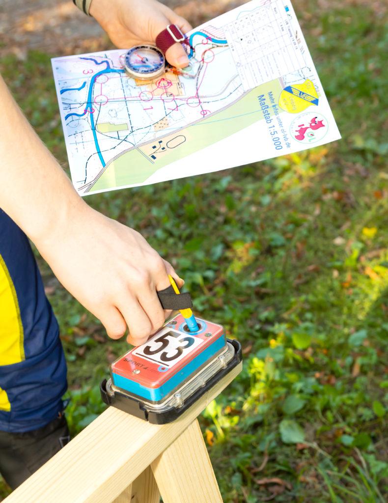 OL-Posten stempeln mit OL-Karte und Kompass